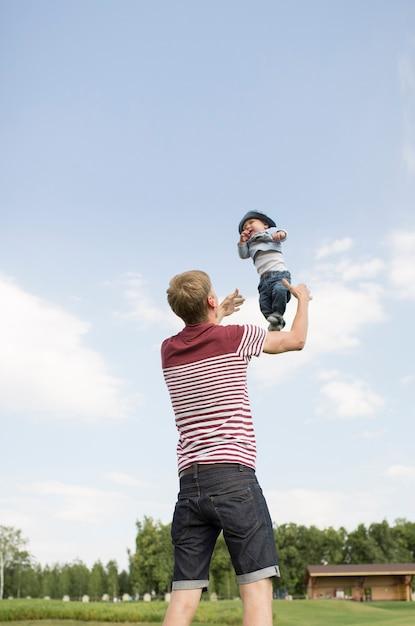 Młody Szczęśliwy Tata Rzuca Swojego Synka W Powietrze I Baw Się Razem. Premium Zdjęcia