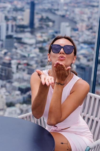 Młody Szczęśliwy Uśmiechnięty Kaukaski Kobieta Podróżnik W Dopasowanej Sukience I Okularach Przeciwsłonecznych Na Wysokim Piętrze W Bangkoku Stylowa Kobieta Odkrywa Niesamowity Widok Na Duże Miasto Darmowe Zdjęcia