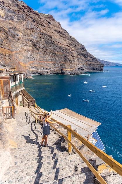 Młody Turysta Schodzący Po Schodach, Aby Dotrzeć Do Zatoki Puerto De Puntagorda, Wyspa La Palma, Wyspy Kanaryjskie. Hiszpania Premium Zdjęcia