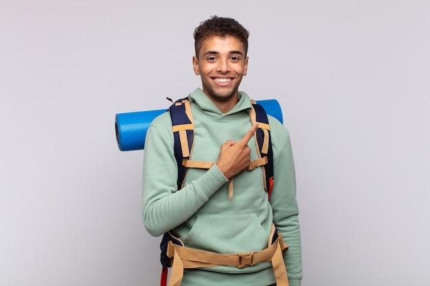 Młody Turysta Uśmiechnięty Wesoło, Czując Się Szczęśliwy I Wskazując Na Bok I Do Góry Premium Zdjęcia