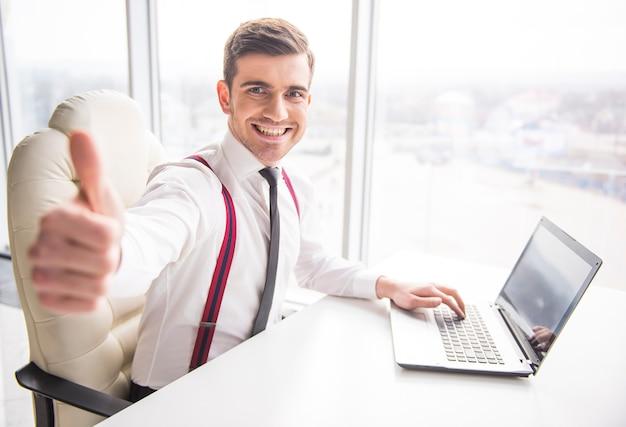 Młody uśmiechnięty biznesmen pokazuje kciuk up. Premium Zdjęcia