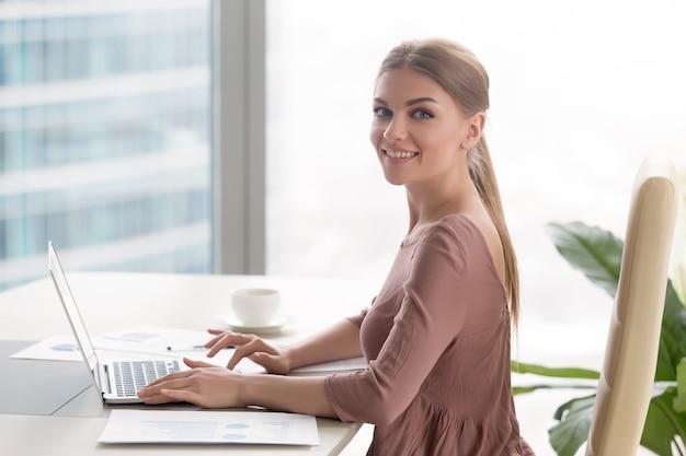 Młody uśmiechnięty bizneswomanu obsiadanie przy biurowym biurkiem patrzeje kamerę Darmowe Zdjęcia