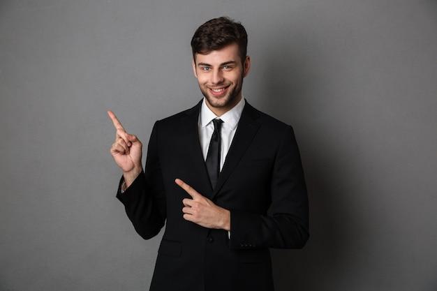 Młody Uśmiechnięty Mężczyzna Brodaty Biznesmen Wskazując Dwoma Palcami W Górę, Darmowe Zdjęcia