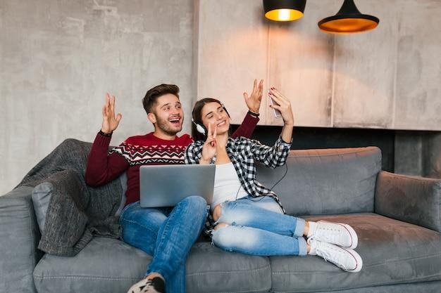 Młody Uśmiechnięty Mężczyzna I Kobieta Siedzą W Domu Zimą, Trzymając Laptopa, Słuchając Słuchawek, Para W Czasie Wolnym Razem, Robiąc Selfie Zdjęcie Aparatem Smartfona, Szczęśliwy, Pozytywny, Randki Darmowe Zdjęcia
