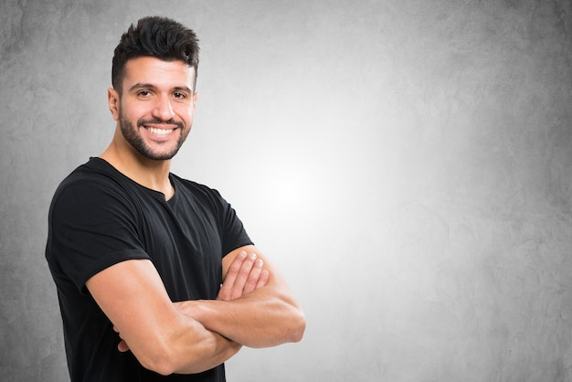 Młody uśmiechnięty mężczyzna przed betonową ścianą Premium Zdjęcia
