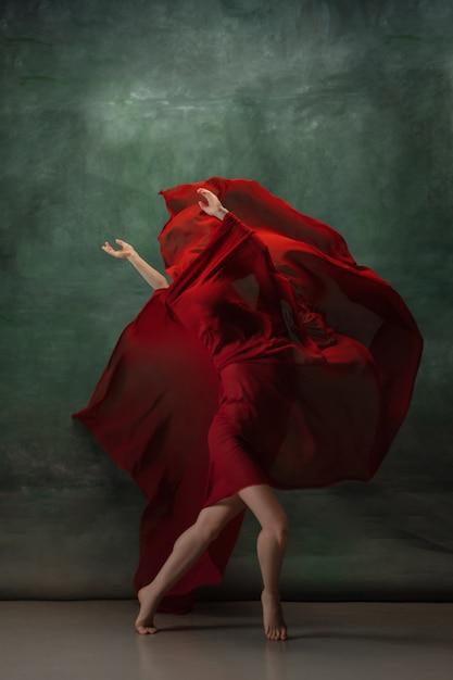 Młody Wdzięczny Baleriny Przetargu Na Ciemnozielonej Przestrzeni Studio Z Czerwonym Suknem Darmowe Zdjęcia
