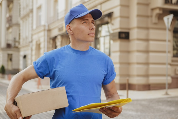 Młody Wesoły Człowiek Dostawy Z Kartonowym Pudełku Na Ulicach Miasta Premium Zdjęcia