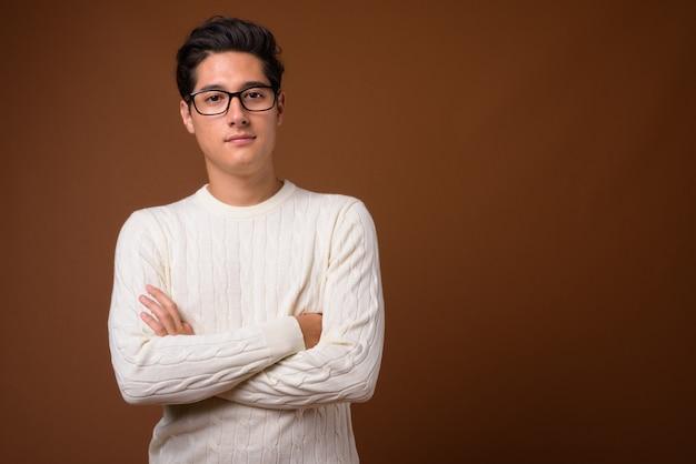 Młody Wieloetniczny Przystojny Mężczyzna Na Brązowym Tle Premium Zdjęcia