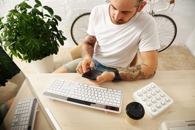 Młody Wytatuowany Freelancer W Pustej Białej Koszulce Używa Swojego Telefonu Komórkowego W Pobliżu Komputera W Domu Przed Murem I Zaparkowanym Zabytkowym Rowerem, Czas Letni Darmowe Zdjęcia