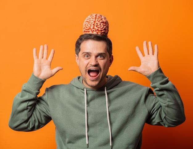 Młody Zaskakujący Facet Z Mózgiem Na Pomarańczowo Premium Zdjęcia