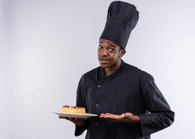 Młody Zaskoczony Afro-amerykański Kucharz W Mundurze Szefa Kuchni Trzyma Ciasto Na Talerzu I Wskazuje Ręką Na Białej ścianie Darmowe Zdjęcia