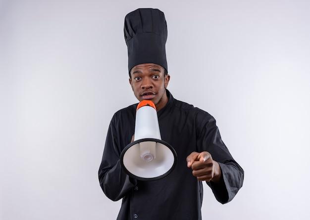 Młody Zaskoczony Kucharz Afro-amerykański W Mundurze Szefa Kuchni Trzyma Głośnik Na Białym Tle Na Białej ścianie Darmowe Zdjęcia