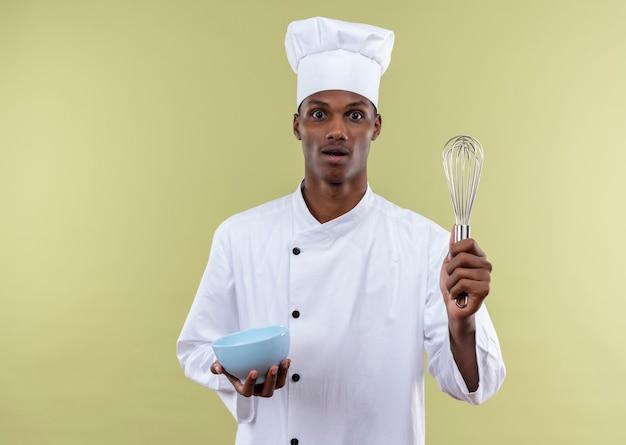 Młody Zaskoczony Kucharz Afro-amerykański W Mundurze Szefa Kuchni Trzyma Miskę I Trzepaczkę Na Białym Tle Na Zielonej ścianie Darmowe Zdjęcia