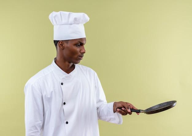 Młody Zaskoczony Kucharz Afro-amerykański W Mundurze Szefa Kuchni Trzyma Patelnię Na Białym Tle Na Zielonej ścianie Darmowe Zdjęcia