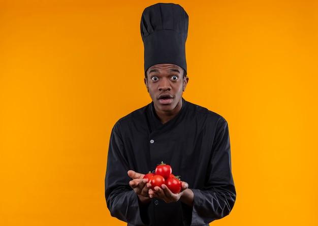 Młody Zaskoczony Kucharz Afro-amerykański W Mundurze Szefa Kuchni Trzyma Pomidory Obiema Rękami Odizolowanymi Na Pomarańczowej ścianie Darmowe Zdjęcia