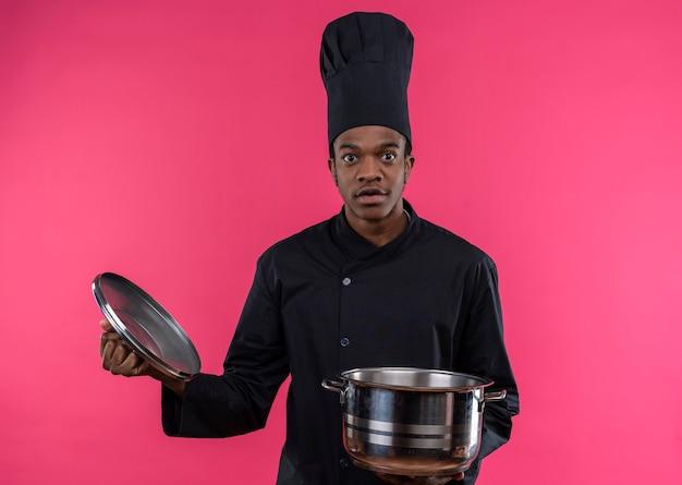 Młody Zaskoczony Kucharz Afro-amerykański W Mundurze Szefa Kuchni Trzyma Rondel Na Białym Tle Na Różowej ścianie Darmowe Zdjęcia