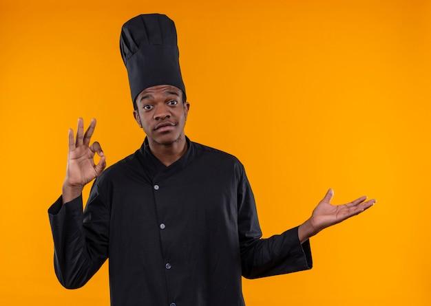 Młody Zaskoczony Kucharz Afroamerykański W Mundurze Szefa Kuchni Gestykuluje Ręką Znak Ok I Wskazuje Na Bok Ręką Odizolowaną Na Pomarańczowej ścianie Darmowe Zdjęcia