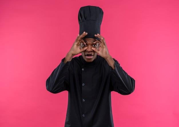 Młody Zaskoczony Kucharz Afroamerykański W Mundurze Szefa Kuchni Otwiera Oczy Rękami Odizolowanymi Na Różowej ścianie Darmowe Zdjęcia