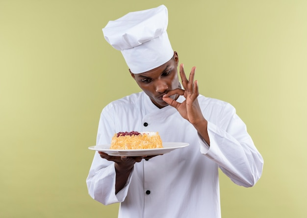 Młody Zaskoczony Kucharz Afroamerykański W Mundurze Szefa Kuchni Patrzy Na Ciasto Na Talerzu I Gestami Smaczne Pyszne Ręką Odizolowaną Na Zielonej ścianie Darmowe Zdjęcia
