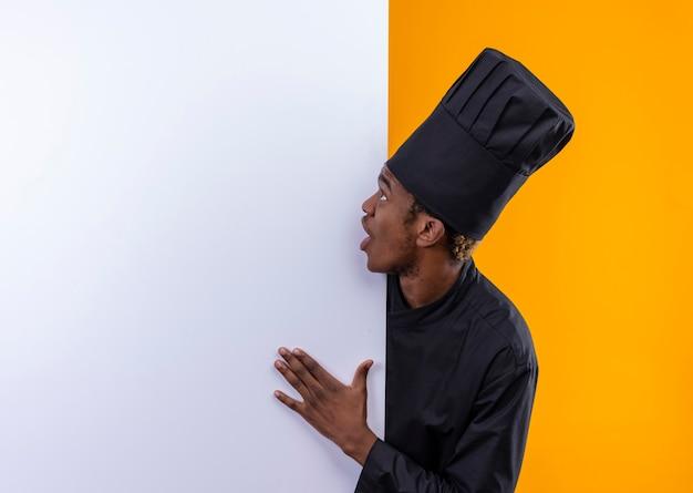 Młody Zaskoczony Kucharz Afroamerykański W Mundurze Szefa Kuchni Stoi Za Białą ścianą I Patrzy Na ścianę Odizolowaną Na Pomarańczowej ścianie Darmowe Zdjęcia