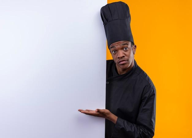 Młody Zaskoczony Kucharz Afroamerykański W Mundurze Szefa Kuchni Stoi Za Białą ścianą I Wskazuje Na ścianę Ręką Odizolowaną Na Pomarańczowej ścianie Darmowe Zdjęcia