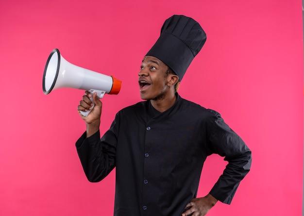 Młody Zaskoczony Kucharz Afroamerykański W Mundurze Szefa Kuchni Trzyma Głośnik Na Różowej ścianie Darmowe Zdjęcia