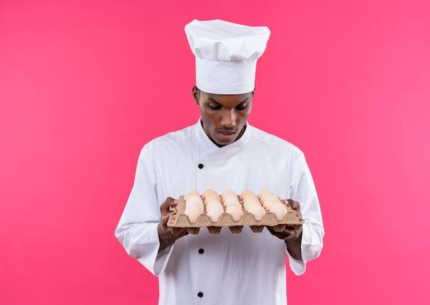 Młody Zaskoczony Kucharz Afroamerykański W Mundurze Szefa Kuchni Trzyma I Patrzy Na Partię świeżych Jaj Na Białym Tle Na Różowej ścianie Darmowe Zdjęcia