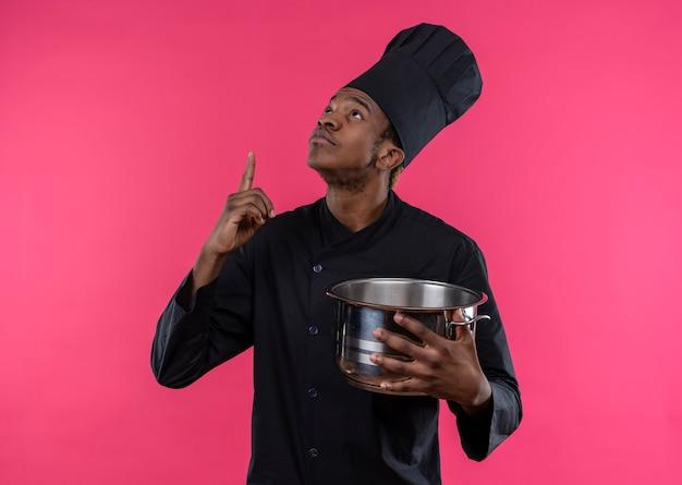 Młody Zaskoczony Kucharz Afroamerykański W Mundurze Szefa Kuchni Trzyma Rondel I Wskazuje W Górę Na Białym Tle Na Różowej ścianie Darmowe Zdjęcia