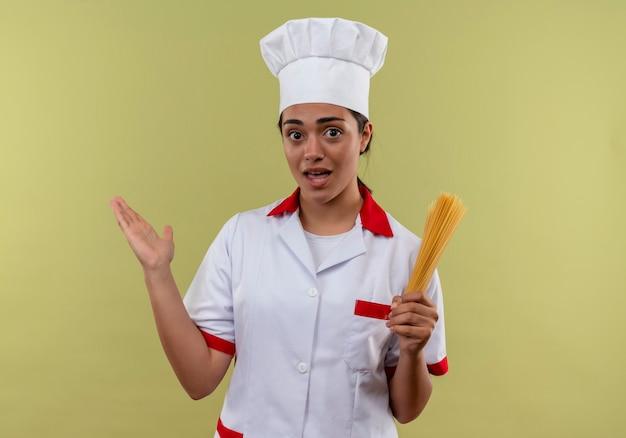 Młody Zaskoczony Kucharz Kaukaski Dziewczyna W Mundurze Szefa Kuchni Trzyma Kilka Spaghetti I Podnosi Rękę Na Białym Tle Na Zielonej ścianie Z Miejsca Na Kopię Darmowe Zdjęcia