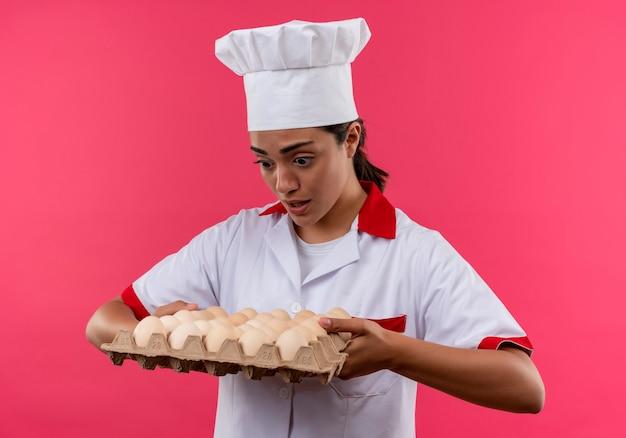 Młody Zaskoczony Kucharz Kaukaski Dziewczyna W Mundurze Szefa Kuchni Trzyma Partię Jaj Na Białym Tle Na Różowej ścianie Z Miejsca Na Kopię Darmowe Zdjęcia