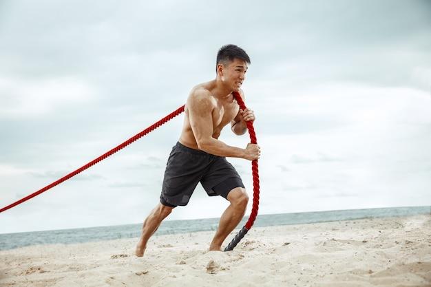 Młody Zdrowy Mężczyzna Sportowiec Robi Przysiady Na Plaży Darmowe Zdjęcia