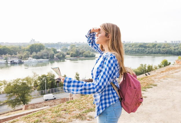 Młody żeński Wycieczkowicz Z Mapą Osłania Jej Oczy Przy Outdoors Darmowe Zdjęcia