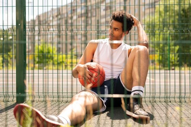 Młody Zrelaksowany Aktywny Mężczyzna Z Piłką Siedzi Przy Ogrodzeniu Boiska Do Koszykówki, Mając Krótką Przerwę Premium Zdjęcia