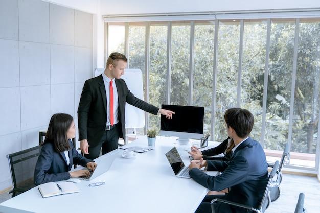 Młodym przedsiębiorcom przedstawiono klientowi projekt pracy marketingowej w biurze pokoju konferencyjnego Premium Zdjęcia