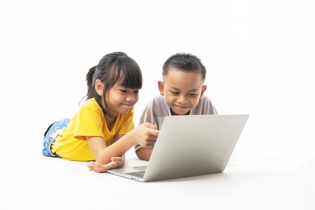 Młodzi azjatyccy tajlandzcy dzieciaki, chłopiec i dziewczyna kłaść i patrzeje na laptopie uczyć się technologią i multimediami Premium Zdjęcia