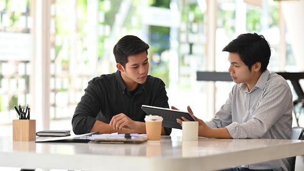 Młodzi biznesowi koledzy opowiada z cyfrową pastylką w nowożytnym biurze. Premium Zdjęcia