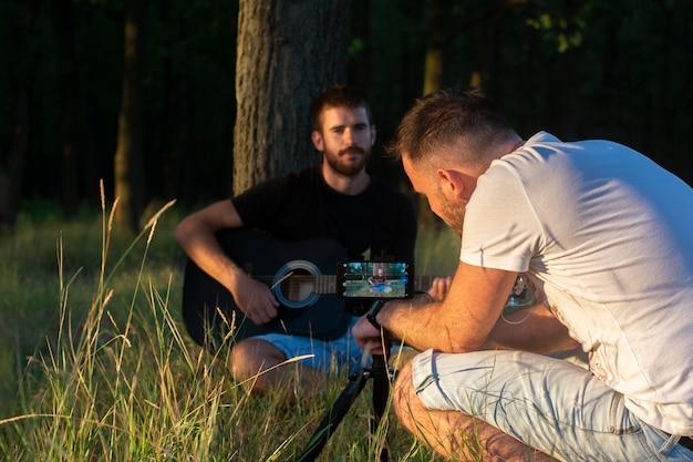 Młodzi Chłopcy Nagrywają Gitarę Na Wideo. Premium Zdjęcia