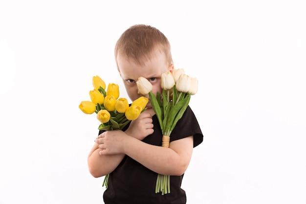 Młodzi Chłopiec Mienia Tulipany Odizolowywający Na Bielu Premium Zdjęcia