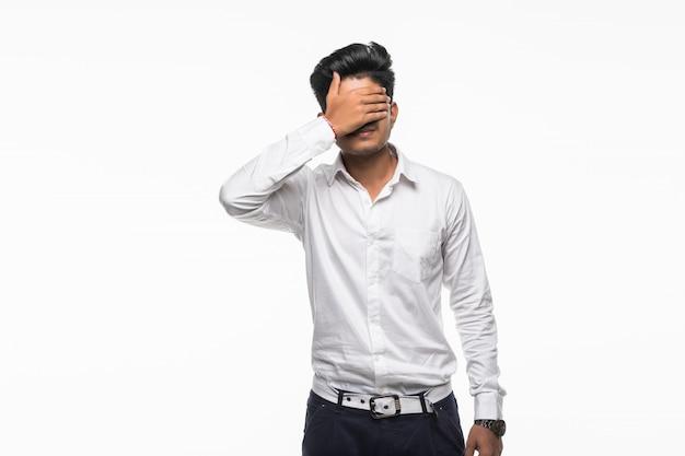 Młodzi Indyjscy Przystojni Mężczyzna Pokrywy Oczy Odizolowywający Na Biel ścianie Darmowe Zdjęcia