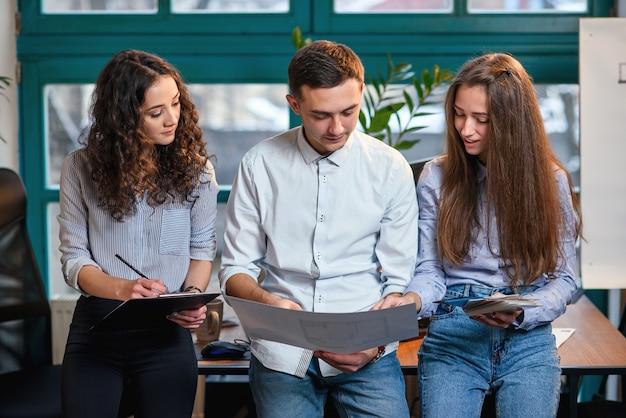 Młodzi Kaukascy Architekci Lub Projektanci Używający Palety Kolorów Do Nowego Projektu Na Laptopie W Stylowym Nowoczesnym Biurze Z Dużym Oknem. Premium Zdjęcia