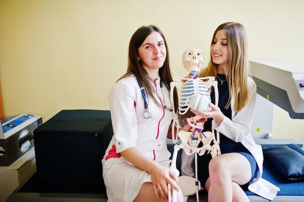 Młodzi lekarze bawią się, stwarzając ze szkieletem. Premium Zdjęcia