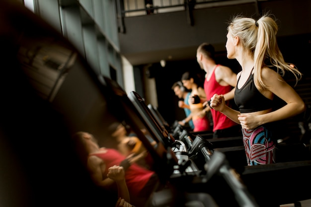 Młodzi ludzie biegają na bieżniach w nowoczesnej siłowni Premium Zdjęcia