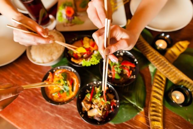 Młodzi ludzie je w tajlandzkiej restauraci Premium Zdjęcia