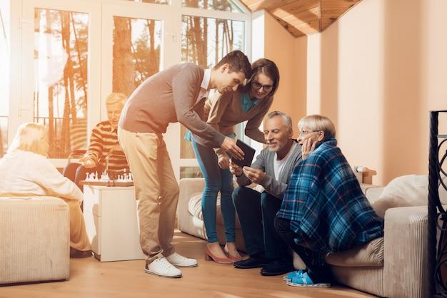 Młodzi Ludzie Przyszli Odwiedzić Starszego Mężczyznę I Kobietę. Premium Zdjęcia
