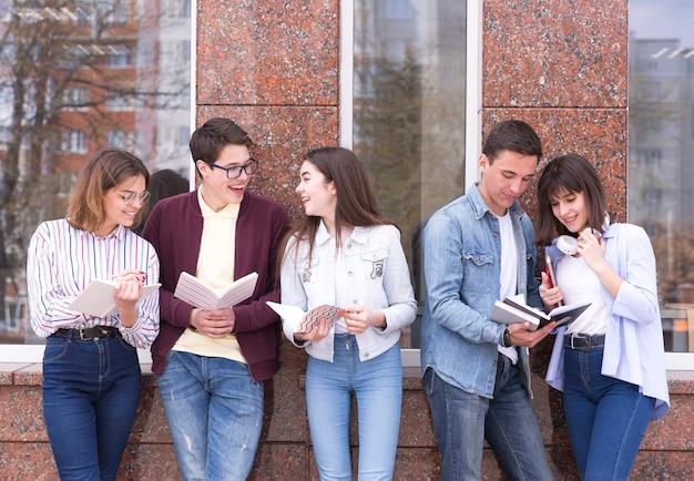 Młodzi ludzie stoi z książkami i czyta je dyskutować zawartość Darmowe Zdjęcia
