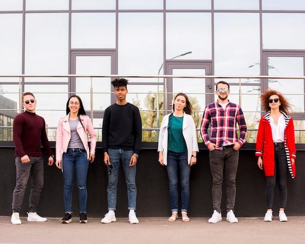 Młodzi Ludzie Stojący W Rzędzie Przed Szklanym Budynkiem Darmowe Zdjęcia