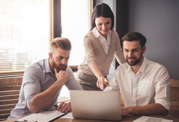 Młodzi ludzie sukcesu firmy używają laptopa. Premium Zdjęcia