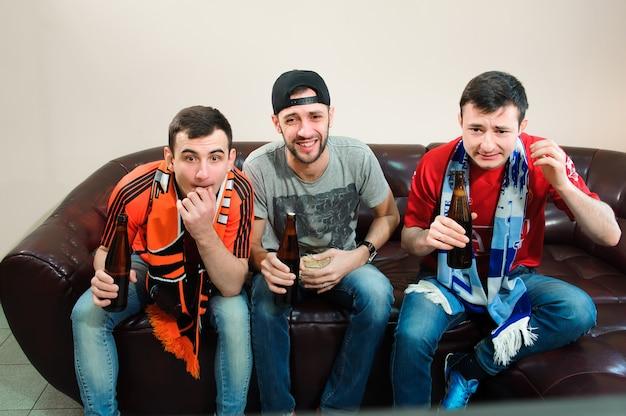 Młodzi Mężczyźni Piją Piwo, Jedzą Chipsy I Korzenie Do Piłki Nożnej Premium Zdjęcia