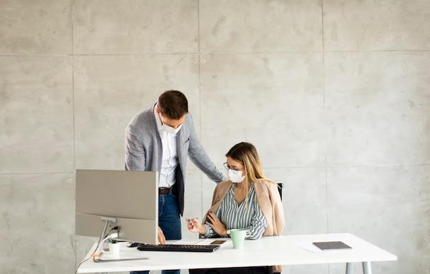 Młodzi Pracownicy Biznesowi Noszą Maski, Aby Chronić I Dbać O Swoje Zdrowie Podczas Pracy Przy Komputerze Premium Zdjęcia