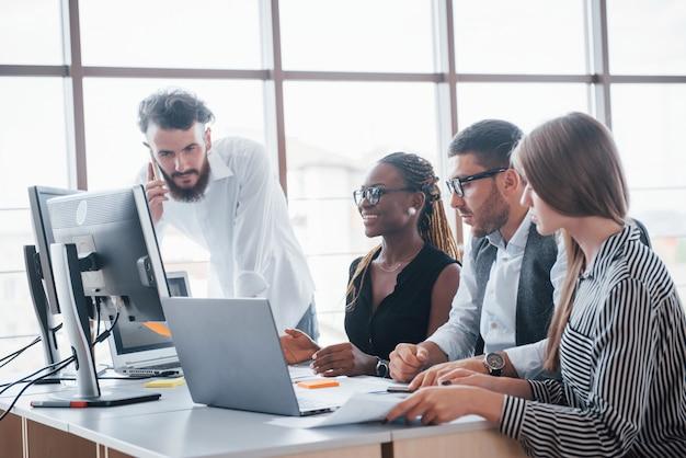 Młodzi Pracownicy Siedzi W Biurze Przy Stole I Używa Laptopu, Pracy Zespołowej Burzy Mózgów Spotkania Pojęcie. Darmowe Zdjęcia